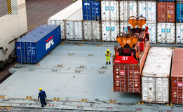 Workers supervising container uploading at dock stock photography