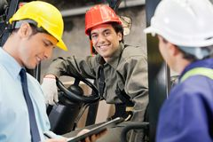 Workers And Supervisors At Warehouse. Portrait of happy young forklift driver with supervisor holding clipboard at warehouse Royalty Free Stock Photos