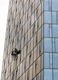 Workers suspended on ropes repairing glass building Stock Photos