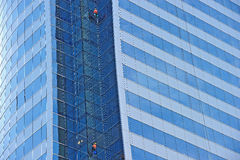 Workers suspended on a scaffold high up on skyscraper Stock Photos
