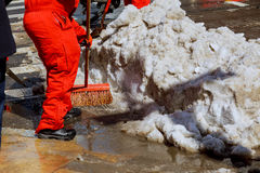 Workers sweep snow from road in winter. Cleaning road from snow storm Stock Image
