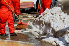 Workers sweep snow from road in winter. Cleaning road from snow storm Royalty Free Stock Photo