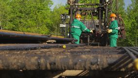 Workers take pipe from truck platform insert into drilling machine by forest