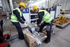 Workers taking aluminium billet Stock Images