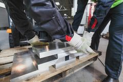 Workers taking aluminium billet. At CNC machine shop Stock Photography