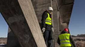 Workers talking under the bridge. In winter day stock video footage