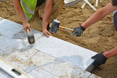 Workers tapping pavers into place with rubber mallets. Installation of granite paver blocks series with motion blur on hammers and hands Royalty Free Stock Photo