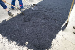 Workers throw asphalt with shovels Royalty Free Stock Photography