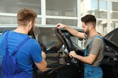 Workers tinting car window with foil