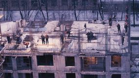 Workers on the top of the building under construction. Time lapse. Workers on the top of the building under construction at the evening in winter stock footage
