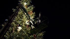Workers on top of Christmas tree decorating in French Christmas capital. Strasbourg, France - circa 2018: low angle view of people on top of telescopic crane in stock video footage