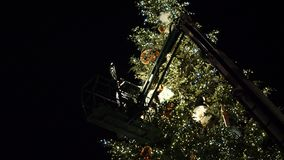 Workers on top of Christmas tree decorating in French Christmas capital. Strasbourg, France - circa 2018: workers on top of telescopic crane in central Place stock footage