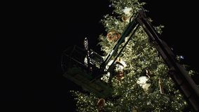Workers on top of Christmas tree decorating in French Christmas capital. Strasbourg, France - circa 2018: workers on top of telescopic crane in central Place stock video footage