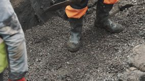 Workers tossing macadam with shovel and boots in ditch. Slowmotion stock video