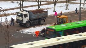 Workers and a tractor to clear snow on the street stock footage