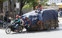 Workers transport goods by motorbike and cart Royalty Free Stock Photography