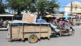 Workers transport goods by motorbike and cart Royalty Free Stock Image