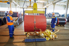 Workers transport metal coil in manufacturing workshop. LOBNYA - JUN 7: Workers transport metal coil in manufacturing workshop at plant of Group of companies Royalty Free Stock Photo