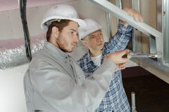 Workers in uniform discussing design construction project Stock Images
