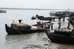 Workers unload cargo from the boat in Gosaba, India Stock Photo