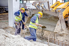 Workers are unloading concrete with shovel from excavator`s fron Stock Photo