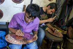 Workers in the Urfa Bazaar in Turkey. Workers in the Urfa (Sanliurfa) bazaar making clocks from a copper base. Urfa is located in the south east of Turkey Stock Photo
