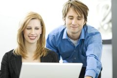 Workers use a computer. Workers happily talk while using a white laptop computer Royalty Free Stock Photography