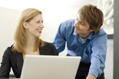 Workers use a computer. Workers happily talk while using a white laptop computer Stock Photo