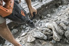 Workers use Electric Concrete Breaker. Male worker repairing driveway surface with jackhammer, digging and drilling stock photo