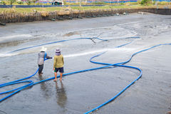 Workers use high pressure water cleaning shrimp pond Stock Image