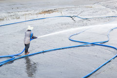 Workers use high pressure water cleaning shrimp pond Royalty Free Stock Images