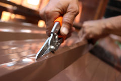 Workers use scissors to cut the metal sheet for roofing. Royalty Free Stock Photo