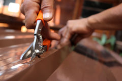 Workers use scissors to cut the metal sheet for roofing. Royalty Free Stock Images