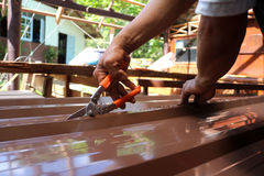 Workers use scissors to cut the metal sheet for roofing. Stock Images