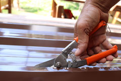 Workers use scissors to cut the metal sheet for roofing. Stock Photos