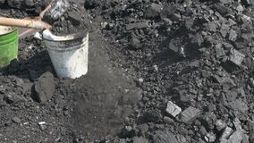 Workers use a shovel to load coal into metal buckets.