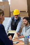 Workers using digital devices in warehouse. On desk Stock Images