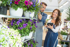 Workers Using Digital Tablet In Flower Shop. Male and female workers using digital tablet in flower shop Stock Photos