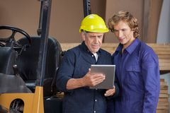 Workers Using Digital Tablet In Workshop Royalty Free Stock Image
