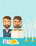 Workers using laptop with windmills. A two caucasian workers using laptop with windmills as power generator.  A Contemporary style with pastel palette, soft Royalty Free Stock Photography
