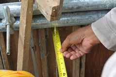 Workers using measuring tape at the construction site Royalty Free Stock Photo