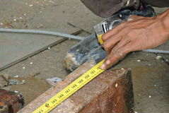 Workers using measuring tape to measure mild steel Royalty Free Stock Images