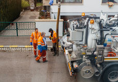 Workers using sewerage truck and large pipe working on the clogg Stock Photo