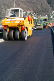 Workers and vehicles during the asphalting of the highway Stock Image