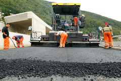 Workers and vehicles during the asphalting of the highway Stock Photography
