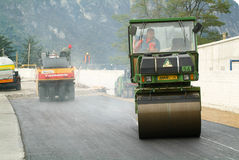 Workers and vehicles during the asphalting of the highway Royalty Free Stock Image