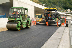 Workers and vehicles during the asphalting of the highway Stock Photos