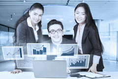 Workers with virtual graph on laptop Royalty Free Stock Photography
