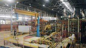 Workers are walking along the industrial hall. stock footage