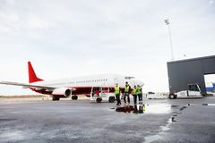 Workers Walking By Airplane On Wet Runway Royalty Free Stock Photos